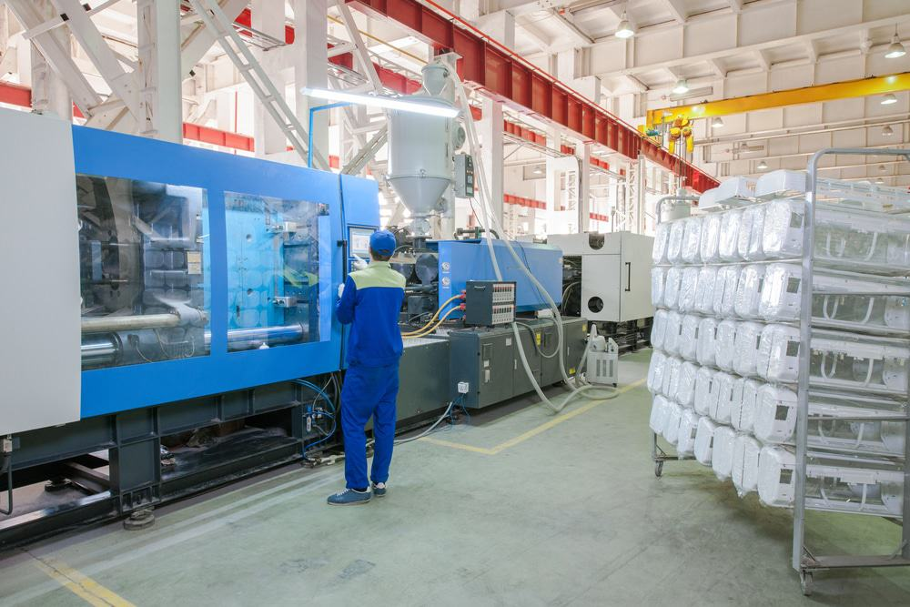Industrial injection molding machine in a manufacturing facility