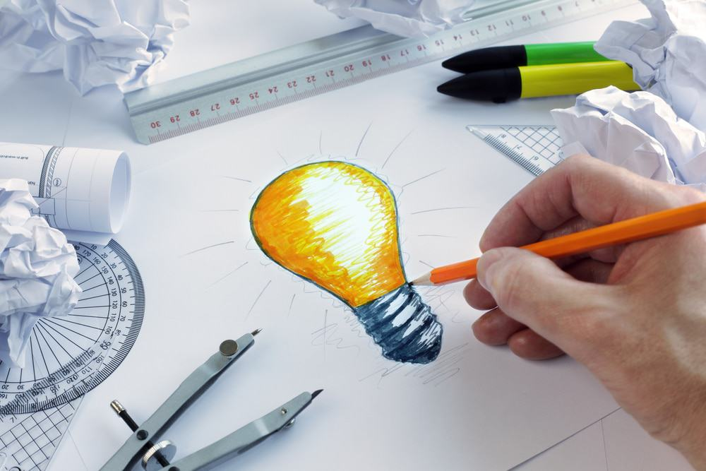 Designer drawing an idea-representing, illuminated light bulb